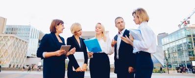 Συνεργάτες επιχειρήσεων που συμβουλεύουν και που καλούν από το smartphone έξω στοκ εικόνες