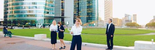 Συνεργάτες επιχειρήσεων που συμβουλεύουν και που καλούν από το smartphone έξω στοκ φωτογραφία