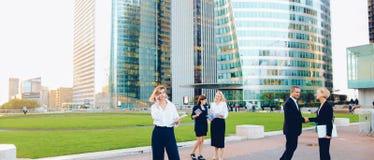 Συνεργάτες επιχειρήσεων που συμβουλεύουν και που καλούν από το smartphone έξω στοκ φωτογραφίες με δικαίωμα ελεύθερης χρήσης