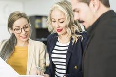 Συνεργάτες που εργάζονται στο γραφείο που φαίνεται έγγραφα στην αρχή στο γραφείο στοκ εικόνα με δικαίωμα ελεύθερης χρήσης