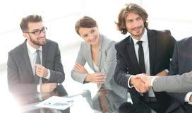 Συνεργάτες χειραψιών σε μια επιχειρησιακή συνεδρίαση Στοκ φωτογραφία με δικαίωμα ελεύθερης χρήσης