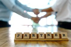 Συνεργάτης λέξης κλειδί στο ξύλινο επιτραπέζιο μέρος της επιχειρησιακής εργασίας Στοκ εικόνες με δικαίωμα ελεύθερης χρήσης