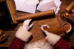 Συνεδρίαση Άγιου Βασίλη στον πίνακα στο δωμάτιο και την επιστολή ή τη λίστα επιθυμητών στόχων Χριστουγέννων γραψίματός του Στοκ φωτογραφία με δικαίωμα ελεύθερης χρήσης