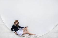 Συνεδρίαση έφηβη στην οδό το άσπρο υπόβαθρο Στοκ Φωτογραφία
