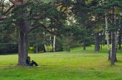 Συνεδρίαση έφηβη στο πλαίσιο του δέντρου και του βιβλίου ανάγνωσης Στοκ φωτογραφίες με δικαίωμα ελεύθερης χρήσης