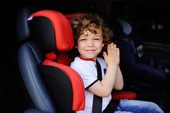 Συνεδρίαση αγοράκι σε ένα κόκκινο κάθισμα αυτοκινήτων παιδιών Στοκ εικόνα με δικαίωμα ελεύθερης χρήσης