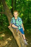 Συνεδρίαση αγοριών από ένα δέντρο Στοκ Φωτογραφία