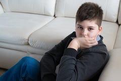 συνεδρίαση αγοριών 13 ετών κοντά στον καναπέ στο δωμάτιο Στοκ φωτογραφία με δικαίωμα ελεύθερης χρήσης