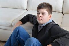 συνεδρίαση αγοριών 13 ετών κοντά στον καναπέ στο δωμάτιο Στοκ Φωτογραφία