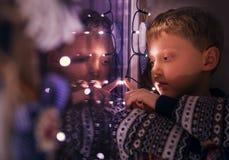Συνεδρίαση αγοριών πορτρέτου κινηματογραφήσεων σε πρώτο πλάνο στο παράθυρο με τα φω'τα Χριστουγέννων Στοκ φωτογραφία με δικαίωμα ελεύθερης χρήσης