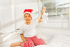 Συνεδρίαση αγοριών σε κακό του στις πυτζάμες και το καπέλο Santa Στοκ Εικόνα