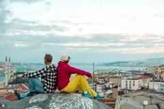 Συνεδρίαση ανδρών και γυναικών πάνω από το κτήριο πόλεων στεγών στοκ εικόνα με δικαίωμα ελεύθερης χρήσης