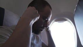 Συνεδρίαση ατόμων κοντά στο παράθυρο του πετώντας αεροπλάνου και του ακούσματος τη μουσική στα ακουστικά με το smartphone σας Μήκ φιλμ μικρού μήκους