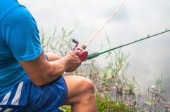 Συνεδρίαση ατόμων που κρατά μια ράβδο αλιείας αλιεύοντας λίμνη Στοκ φωτογραφία με δικαίωμα ελεύθερης χρήσης