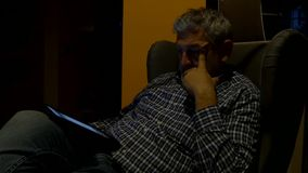 Συνεδρίαση ατόμων που φαίνεται ταμπλέτα τη νύχτα 4K απόθεμα βίντεο