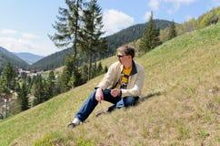 Συνεδρίαση ατόμων σε ένα απότομο βουνό Στοκ φωτογραφία με δικαίωμα ελεύθερης χρήσης