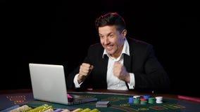 Συνεδρίαση ατόμων σε ένα lap-top και παιχνίδι στις σε απευθείας σύνδεση χαρτοπαικτικές λέσχες κλείστε επάνω απόθεμα βίντεο