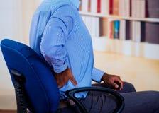 Συνεδρίαση ατόμων σε μια καρέκλα, που βάζει το χέρι του στην πλάτη του, σήμα πόνου Στοκ Φωτογραφίες