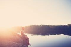 Συνεδρίαση ατόμων στην άκρη του απότομου βράχου κοντά στη λίμνη μετά από να κολυμπήσει και να κοιτάξει μακριά Στοκ Εικόνες