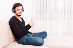 Συνεδρίαση ατόμων στον καναπέ που φορά τα ακουστικά που παρουσιάζουν αντίχειρα Στοκ Εικόνες