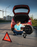 Συνεδρίαση ατόμων στο δρόμο και κλίση ενάντια στο σπασμένο αυτοκίνητο Στοκ Φωτογραφίες