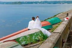 Συνεδρίαση γαμήλιων ζευγών πίσω, μεταξύ των παλαιών βαρκών κοντά στον ποταμό Στοκ Εικόνες