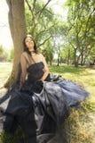 Συνεδρίαση γαμήλιων μπλε φορεμάτων γυναικών νυφών Brunette κοντά στο δέντρο στοκ φωτογραφίες