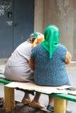 Συνεδρίαση γιαγιάδων κουτσομπολιού δύο στον πάγκο και την είσοδο στοκ φωτογραφία