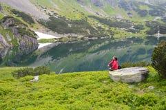 Συνεδρίαση γυναικών κοντά στη λίμνη στα βουνά Στοκ Εικόνες