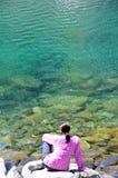 Συνεδρίαση γυναικών κοντά στη λίμνη στα βουνά Στοκ φωτογραφία με δικαίωμα ελεύθερης χρήσης