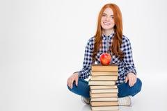 Συνεδρίαση γυναικών κοντά στο σωρό των βιβλίων με το μήλο στην κορυφή Στοκ Εικόνες