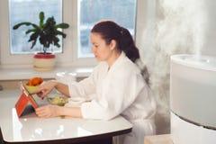 Συνεδρίαση γυναικών με το PC ταμπλετών στο υπόβαθρο του υγραντή Στοκ Φωτογραφία