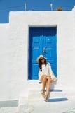 Συνεδρίαση γυναικών μπροστά από μια μπλε εκλεκτής ποιότητας πόρτα εισόδων στοκ εικόνες