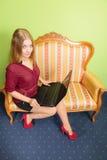 Συνεδρίαση γυναικών μόδας στον καναπέ που χρησιμοποιεί το lap-top PC Στοκ Εικόνες