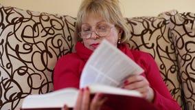 Συνεδρίαση γυναικών σε ένα κτύπημα καναπέδων μέσω των σελίδων ενός μεγάλου βιβλίου απόθεμα βίντεο