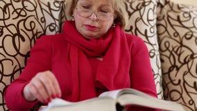 Συνεδρίαση γυναικών σε ένα κτύπημα καναπέδων μέσω των σελίδων ενός μεγάλου βιβλίου φιλμ μικρού μήκους