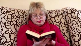 Συνεδρίαση γυναικών σε ένα ντιβάνι και ανάγνωση ένα βιβλίο φιλμ μικρού μήκους