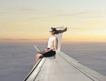 Συνεδρίαση γυναικών σε ένα φτερό αεροπλάνων Στοκ Φωτογραφία