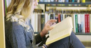 Συνεδρίαση γυναικών σπουδαστών στο πάτωμα και ανάγνωση ένα βιβλίο στη σχολική βιβλιοθήκη απόθεμα βίντεο