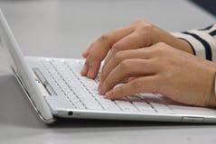Συνεδρίαση γυναικών στη δακτυλογράφηση γραφείων στο πληκτρολόγιο ενός άσπρου lap-top Στοκ φωτογραφία με δικαίωμα ελεύθερης χρήσης