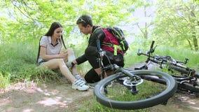 Συνεδρίαση γυναικών στη χλόη μετά από το ατύχημα ποδηλάτων απόθεμα βίντεο