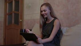 Συνεδρίαση γυναικών στον καναπέ και χρησιμοποίηση του lap-top απόθεμα βίντεο