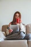 Συνεδρίαση γυναικών στον καναπέ με την ταμπλέτα και τον καφέ υπό εξέταση Στοκ Εικόνα
