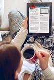 Συνεδρίαση γυναικών στον καναπέ με την ταμπλέτα και τον καφέ υπό εξέταση Στοκ Εικόνες