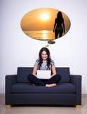 Συνεδρίαση γυναικών στον καναπέ, χρησιμοποιώντας το lap-top και ονειρεμένος για το καλοκαίρι Στοκ φωτογραφία με δικαίωμα ελεύθερης χρήσης