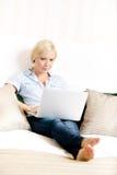 Συνεδρίαση γυναικών στο κρεβάτι με το lap-top Στοκ φωτογραφία με δικαίωμα ελεύθερης χρήσης