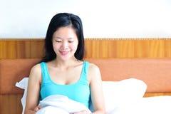 Συνεδρίαση γυναικών στο κρεβάτι που χρησιμοποιεί την ταμπλέτα της Στοκ φωτογραφίες με δικαίωμα ελεύθερης χρήσης