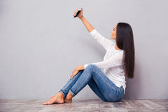 Συνεδρίαση γυναικών στο πάτωμα και παραγωγή selfie της φωτογραφίας Στοκ φωτογραφία με δικαίωμα ελεύθερης χρήσης