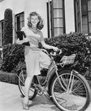 Συνεδρίαση γυναικών στο ποδήλατό της με ένα βιβλίο στα όπλα της (όλα τα πρόσωπα που απεικονίζονται δεν ζουν περισσότερο και κανέν στοκ εικόνες