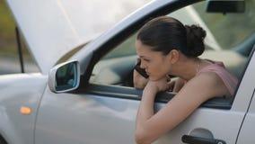 Συνεδρίαση γυναικών στο σπασμένο αυτοκίνητο που απαιτεί τη βοήθεια απόθεμα βίντεο
